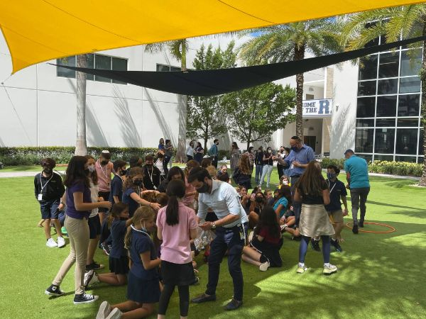 image of students gathering in masks in the school covered courtyard